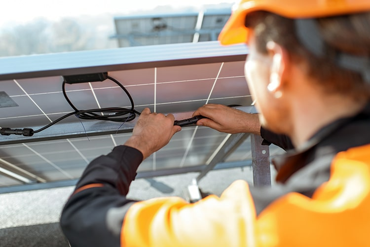 Electrician doing solar power maintenance on panels on a rooftop photovoltaic power plant.