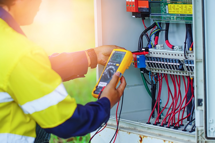 Workers use Multimeter to measure the voltage of electrical wires produced from solar energy.
