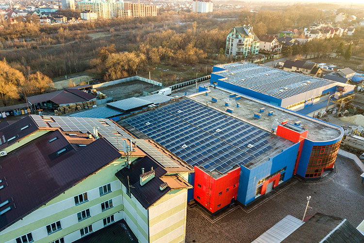 Aerial view of many photo voltaic solar panels mounted of industrial building roof.